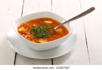 Image of bowl of hot red soup isolated on white wooden table