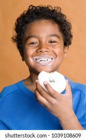 An image of Boy eating a doughnut