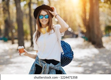 Image of a bright smiling hipster girl with brown hair wearing a hat, sunglasses and backpack holding cup of tea or coffee in the park