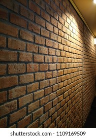 Image of brown brick wall texture with lighting on top for vintage or earthtone background concept