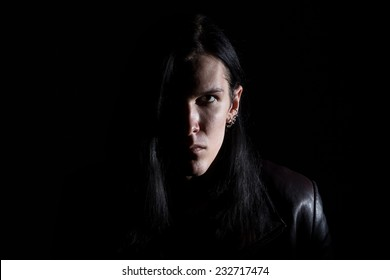 Image of the brunet man with long hair on black background