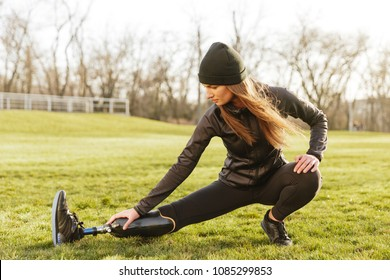 Image of brunette disabled athletic girl in sportswear doing sports and stretching prosthetic leg on grass