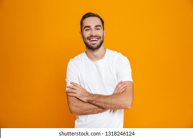 Image of brunette man 30s with beard and mustache smiling while standing isolated over yellow background