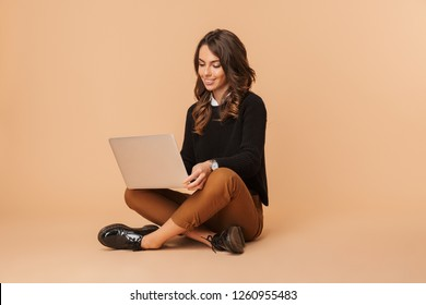 Image of brunette woman 20s using laptop while sitting on floor isolated over beige background