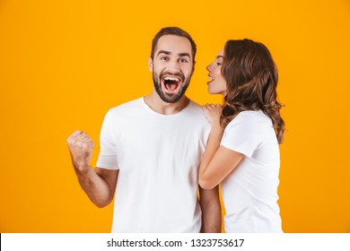 Image of brunette woman whispering secret or interesting gossip to man in his ear isolated over yellow background