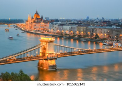 Image of Budapest cityscape with Parliament building and famous Chain Bridge illuminated with lights during sunset on Danube river
