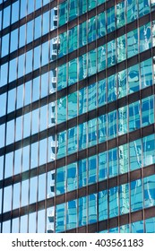 Image of building exterior with reflection of another building in windows