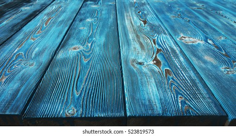 Image of bumpy vintage wooden tabletop painted with blue paint