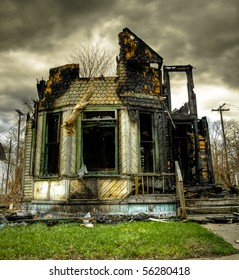 Image of a burned abandoned house in an urban setting with overcast sky.