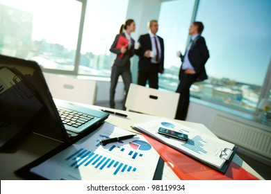 Image of business documents on workplace with associates talking on background