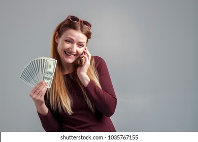The image of a business girl, earning by phone. A strong independent woman speaks on the phone with money in her hands.