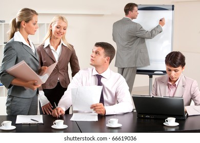 Image of business group discussing new project during break in the office