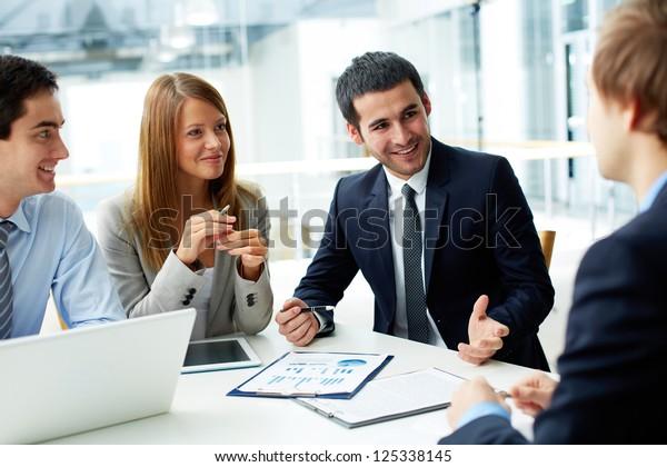 会議でドキュメントやアイデアを議論するビジネス・パートナーの画像