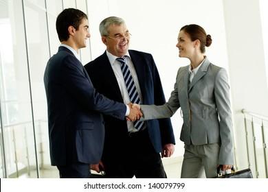 Image of business partners handshaking after striking deal