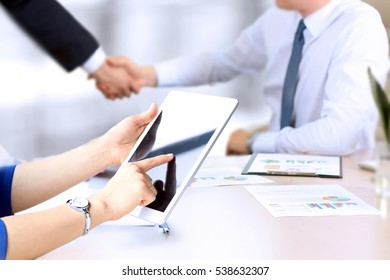 Image of business partners handshaking over business objects on workplace. businesswoman working with digital tablet