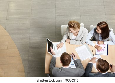 Image of business partners sitting at table and planning work