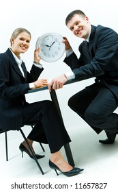 Image of business people holding the clock together and smiling