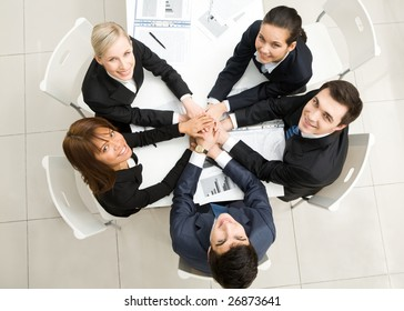 Image of business people with their hands on top of each other and looking upwards