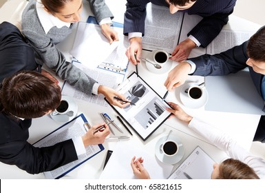 Image of business team sitting at the table and discussing a new project