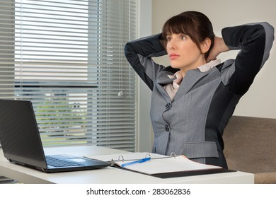 The image of business woman doing exercise at the office