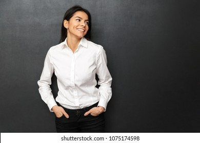 Image of businesslike cheerful woman wearing formal outfit smiling and posing with arms in pockets while looking aside isolated over dark gray background