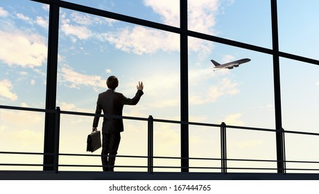 Image of businessman at airport looking at airplane taking off