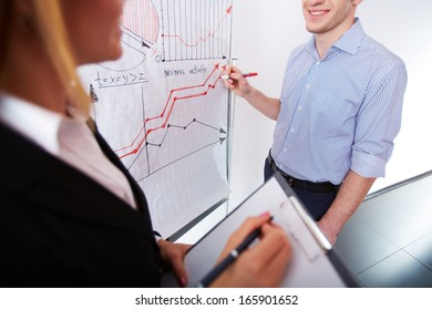 Image of businessman analyzing graph on whiteboard and his colleague