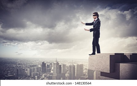 Image of businessman in blindfold standing on top of building