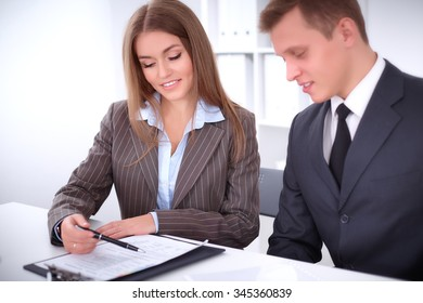 Image of businessman and business woman using clipboard  at meeting