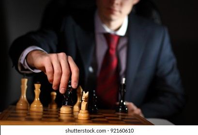 Image of a businessman in dark suit playing chess