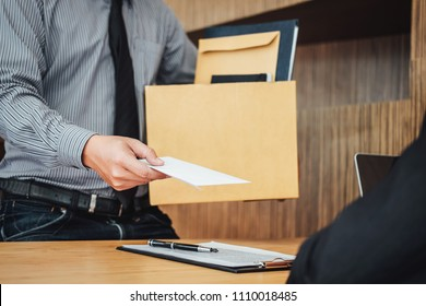 Image of businessman hand holding cardboard box and sending a resignation letter to his boss, change of job, unemployment, resign concept.