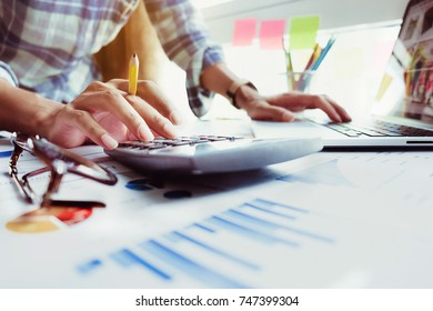 Image of Businessman hand holding pencil and financing, calculating with calculator and laptop computer on office desk, Business Accountant concept.