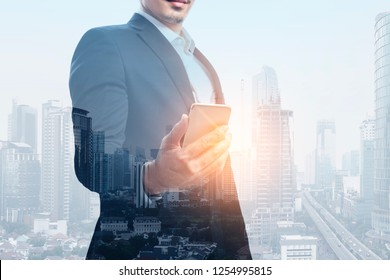 Image of businessman holding smart phone on the city with sunlight background. Double exposure