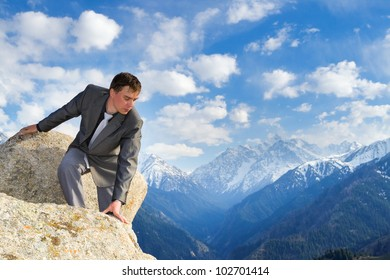 Image of a businessman standing on the top of the mountain, looking down. In the background a beautiful panorama of the valley with high peaks.