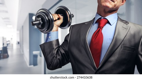 Image of businessman in suit raising dumbbell in office. Tax burden concept