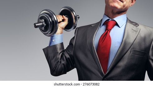 Image of businessman in suit raising dumbbell. Tax burden concept