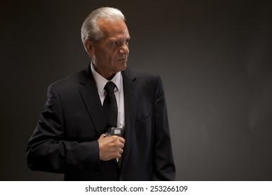 Image of businessman taking out handgun and looking away