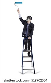 Image of a businessman wearing a gas mask and standing on the ladder while using a paint roller