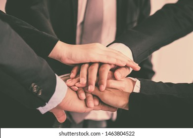 Image of businesspeople hands on top of each other as symbol of their partnership. Multiethnic businesspeople working together. Collaboration in Business Team success. StrongTeamwork concept.