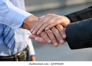 Image of businesspeople hands on top of each other as symbol of their partnership.Cropped image of young business team holding hands together.
