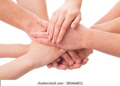 Image of businesspeople symbolizing successful team. Different people holding their hands alltogether isolated on white background.