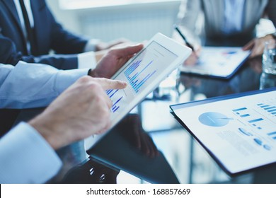 Image of businessperson pointing at document in touchpad at meeting