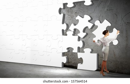 Image of businesswoman connecting elements of white puzzle