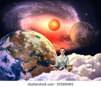 image of a businesswoman meditating in the clouds in space. Elements of this image furnished by NASA