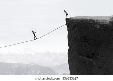 Image of businesswoman taking risk and walking on the rope over the gap