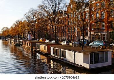 Image of a canal with specific floating houses in Amsterdam during an autumn afternoon.