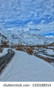the image is captured on afternoon and the place is called suru valley in kargil ladakh jammu and kashmir india,a road on the left and river on the right with snow covered plains and mountains