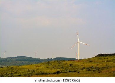 The image was captured at Satara district in Maharashtra state, India. It shows an isolated wind turbine on a plateau.