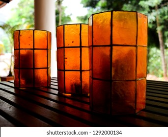 The image captures three plastic glasses of Orange colour kept on a wooden table.