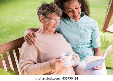 Image of caregiver and senior resting in the garden